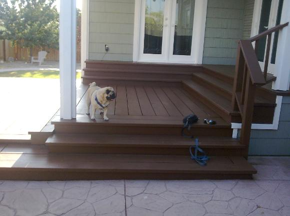 Backyard home remodel Stained two tiered deck with steps to French doors